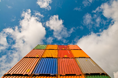 Containers viewed from below with blue sky and clouds